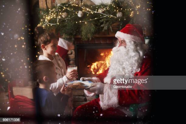 young girl and boy giving milk and cookies to santa - santa close up stock pictures, royalty-free photos & images