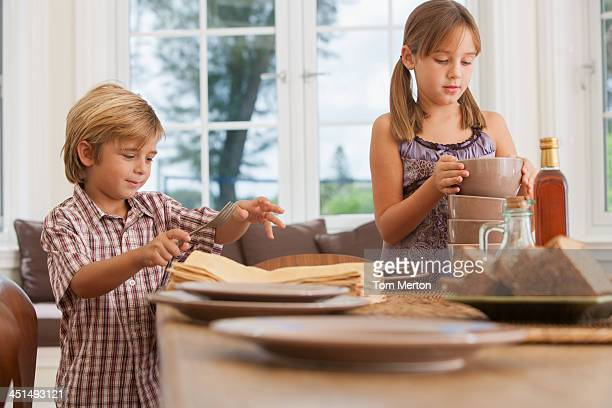 Young girl and boy in dining room setting table