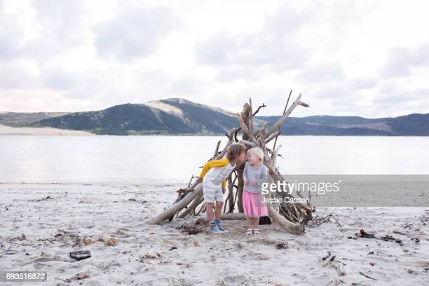 Young girl and boy kissing on a beautiful beach in a driftwood teepee