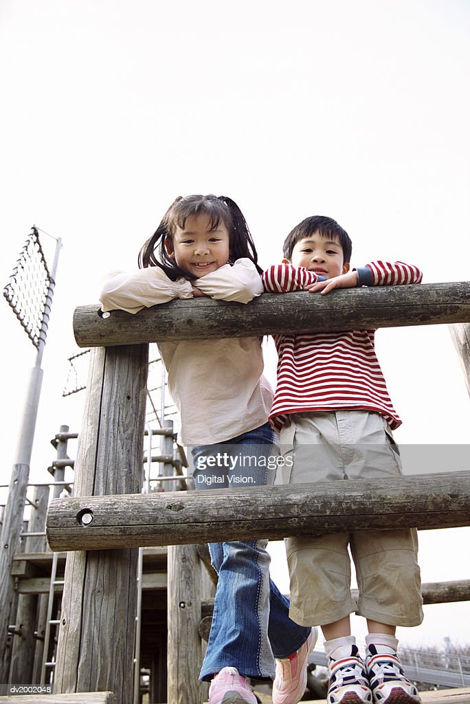 Young Girl and Boy Leaning Against a Wooden Fence on an Adventure Playground : Stock Photo