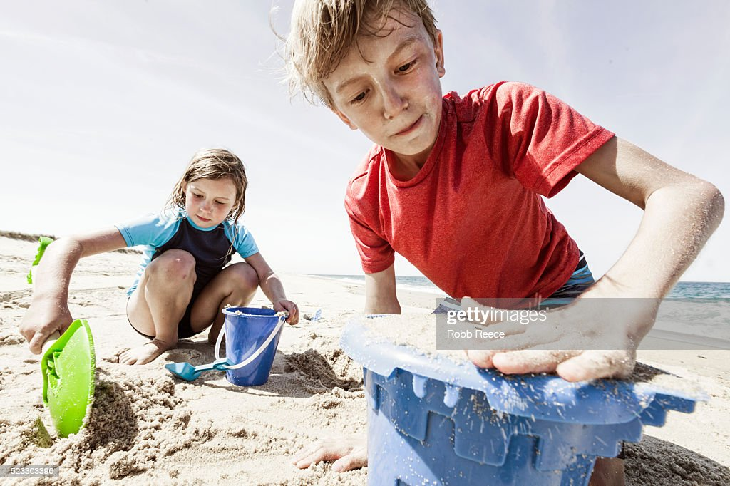 A young girl and boy playing with toys and digging sand on a Nantucket beach : Stock Photo