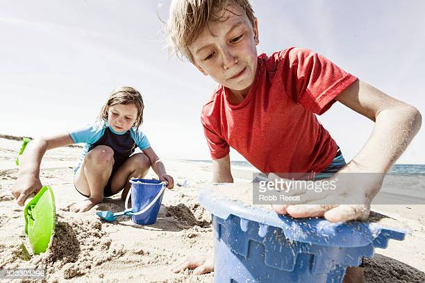 a young girl and boy playing with toys and digging sand on a nantucket beach - robb reece stock-fotos und bilder