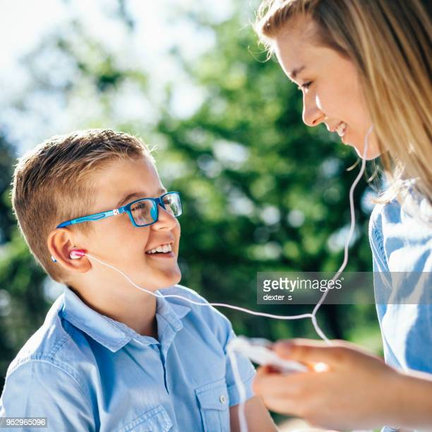 Jeune fille et garçon partage musique de téléphone intelligent