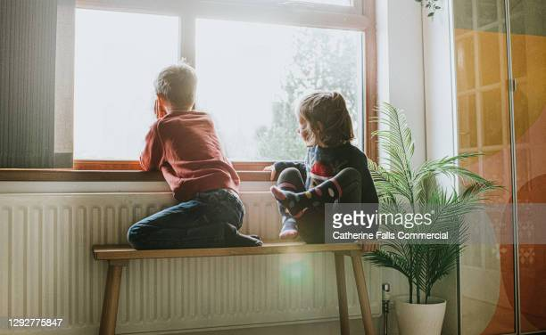 young girl and boy sit on a bench by a sunny window and gaze out - temperature stock pictures, royalty-free photos & images