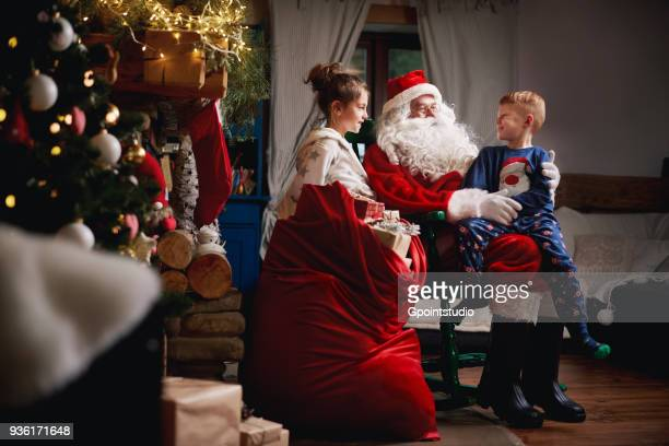 young girl and boy sitting with santa, sack full of presents beside him - grotto stock pictures, royalty-free photos & images