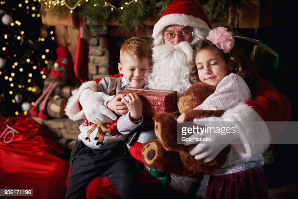young girl and boy visiting santa, holding gifts - grotto stock pictures, royalty-free photos & images