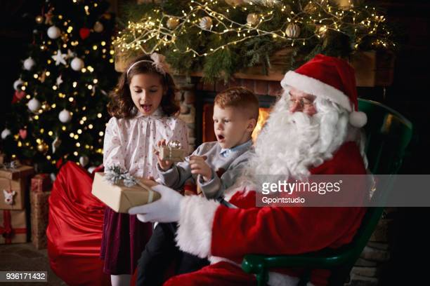 young girl and boy visiting santa, receiving gifts - grotto stock pictures, royalty-free photos & images