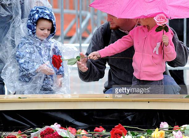 A young girl and boy with a man squats in the rain at the reflecting pool placing flowers as people gather at Ground Zero during a 9/11 memorial...
