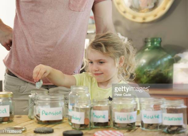 young girl and father putting money into savings jars - finance and economy stock pictures, royalty-free photos & images