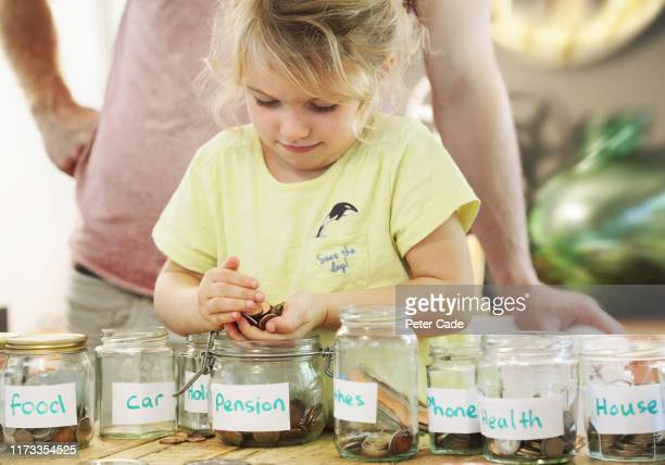 young girl and father putting money into savings jars - finance stock pictures, royalty-free photos & images