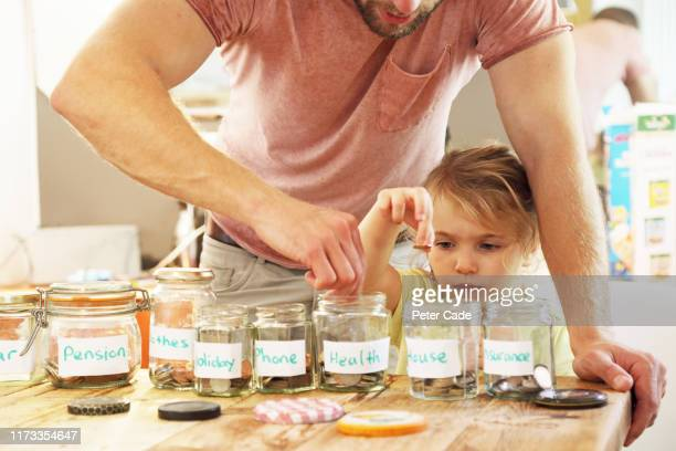 young girl and father putting money into savings jars - ersparnisse stock-fotos und bilder