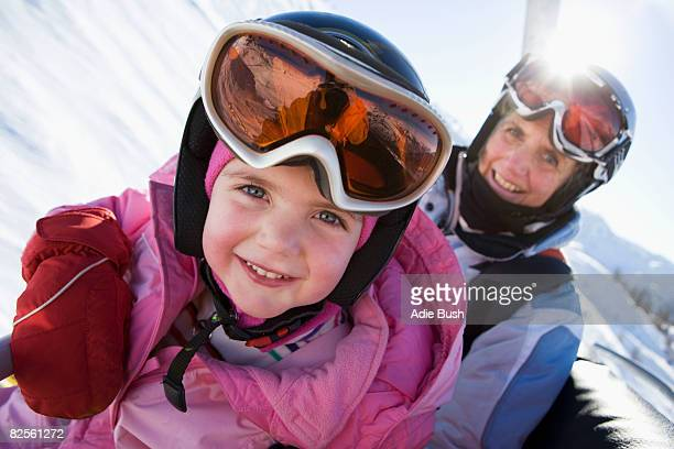 young girl and grandmother on chair lift - sport d'hiver photos et images de collection