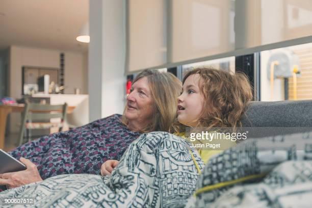 Young girl and grandmother on sofa
