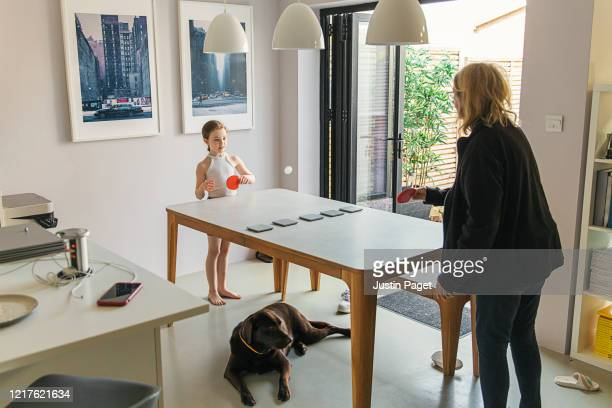 young girl and grandmother playing table tennis on dining table - makeshift stock pictures, royalty-free photos & images