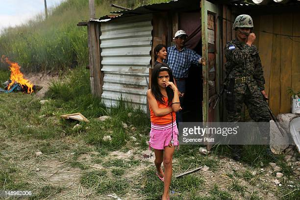A young girl and her family stand by their home as police and the army force them and their neighbors to dismantle the shanty town after the...