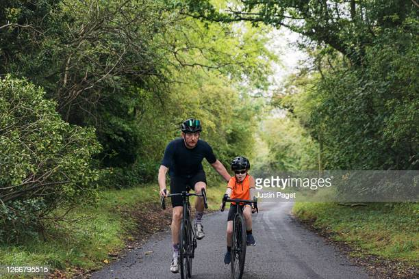 young girl and her father are out cycling in the country side. - hill stock pictures, royalty-free photos & images