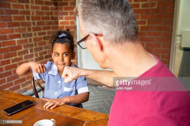 young girl and her father in their dining room - thisisaustralia stock pictures, royalty-free photos & images