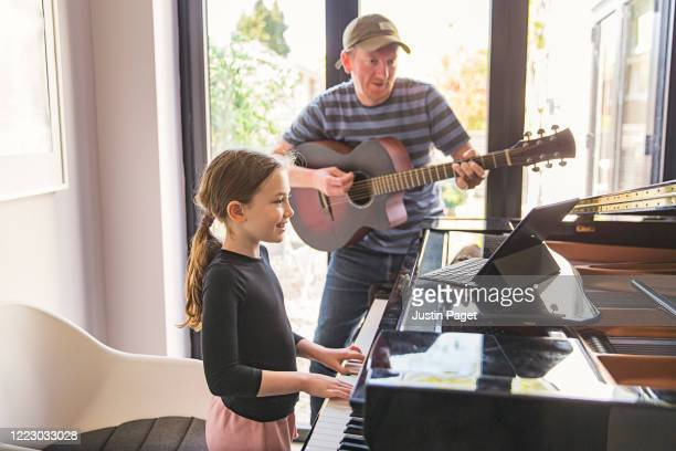 young girl and her father play a song together - skill stock pictures, royalty-free photos & images