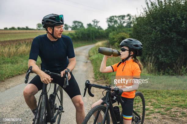 young girl and her father take a break from cycling - endurance stock pictures, royalty-free photos & images