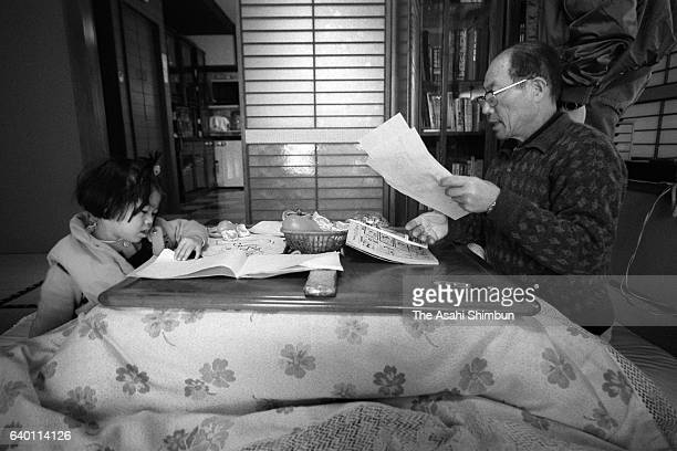 A young girl and her grand father spend time in a kotatsu heater equipped table on February 14 1999 in Katsunuma Yamanashi Japan