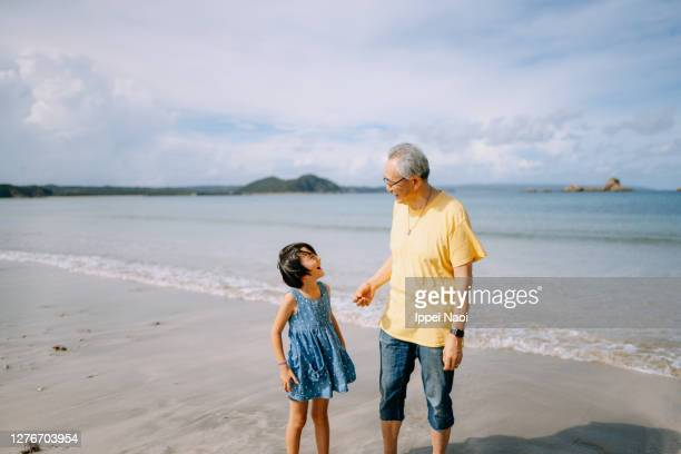 young girl and her grandfather playing on beach, japan - 祖父 ストックフォトと画像
