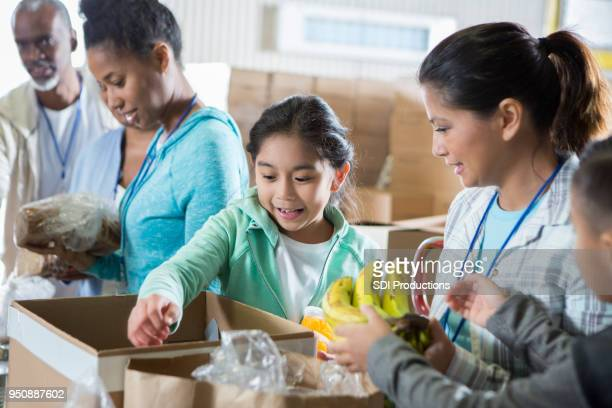young girl and her mom volunteer during food drive - food pantry stock pictures, royalty-free photos & images