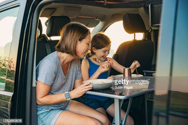 young girl and her mother eating dinner in their camper van - travel stock pictures, royalty-free photos & images