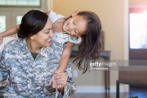 young girl and her mother play with one another - military stock pictures, royalty-free photos & images