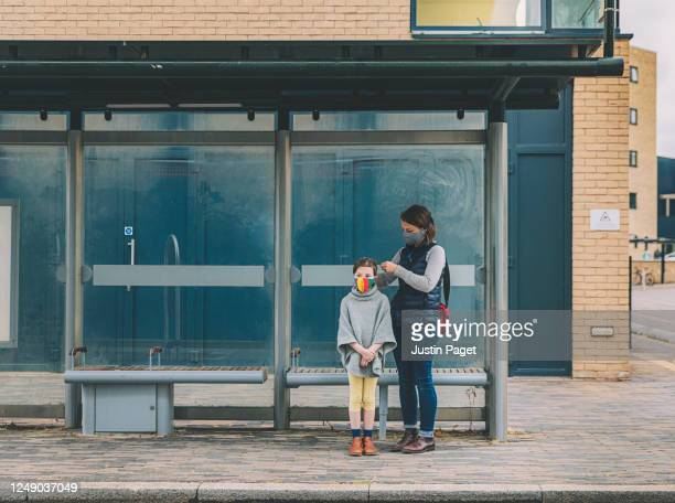 young girl and her mother waiting for the bus. they both wear masks - gender stock pictures, royalty-free photos & images