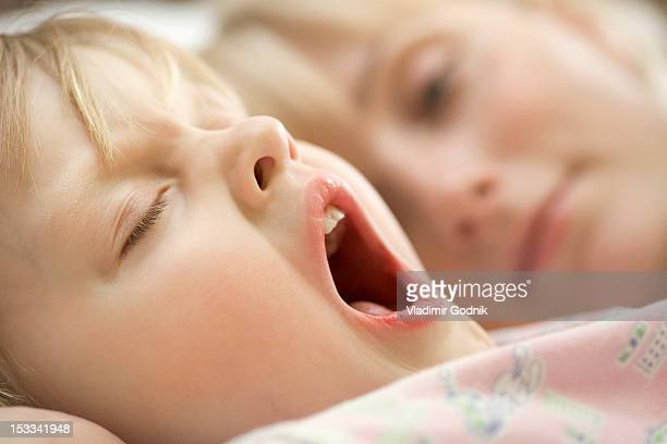 a young girl and her mother waking up in the morning - yawning mother child stock photos and pictures