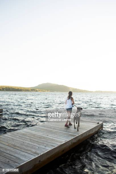 young girl and her trusty dog on the dock - moosehead lake stock photos and pictures
