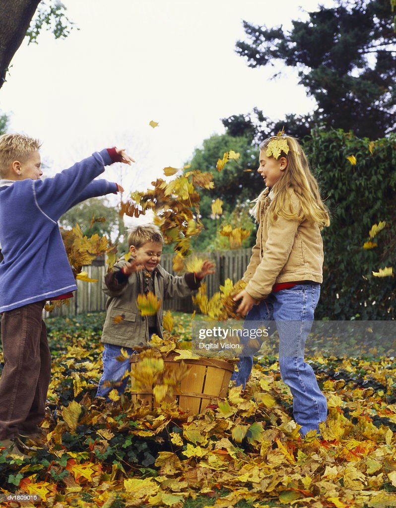 Young Girl and Her Two Brothers Stand in Their Garden Throwing Autumn Leaves From a Basket : Stock Photo
