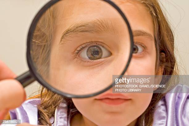 Young girl and magnifying glass