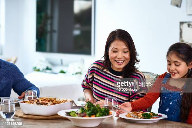 young girl and mother enjoying healthy meal together - vietnamese ethnicity stock pictures, royalty-free photos & images