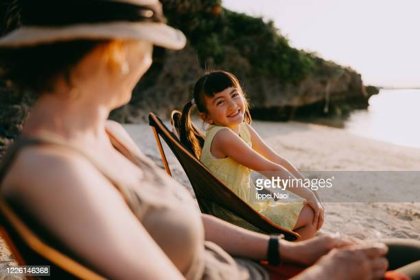 Young girl and mother having fun at beach campsite, Japan