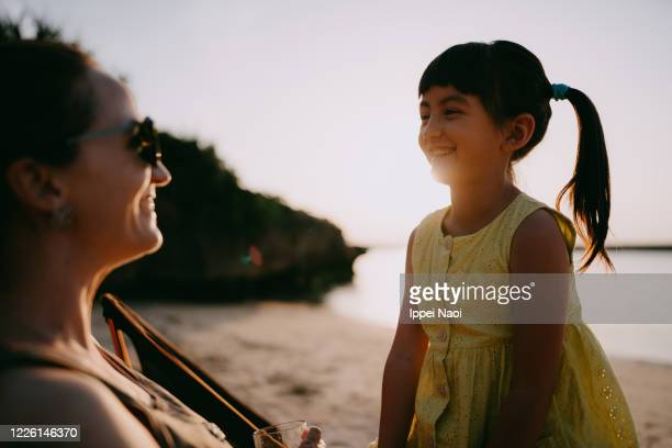 young girl and mother having fun at beach campsite, japan - ippei naoi stock pictures, royalty-free photos & images
