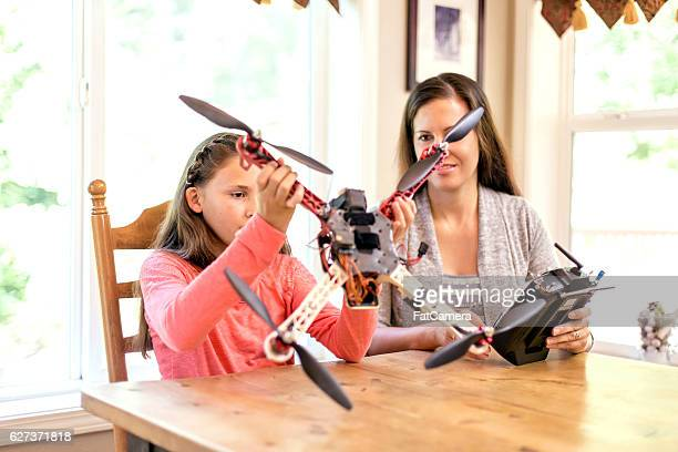 Young girl and mother looking at a drone and controller