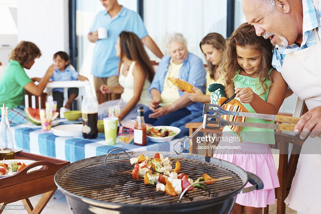 Young girl and older man grilling at barbecue : Stock Photo
