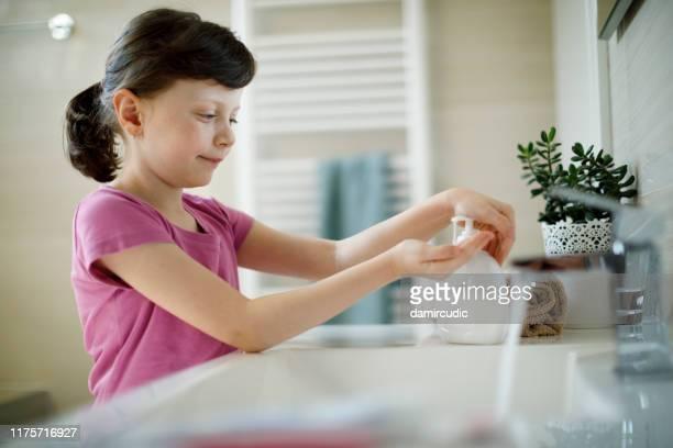 jong meisje het toepassen van antiseptische hand sanitizer - hand sanitizer stockfoto's en -beelden