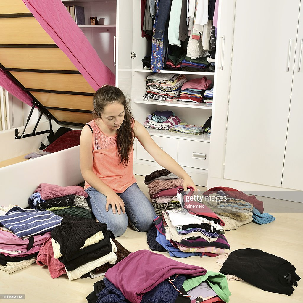 Young girl arranging her clothes : Stock Photo