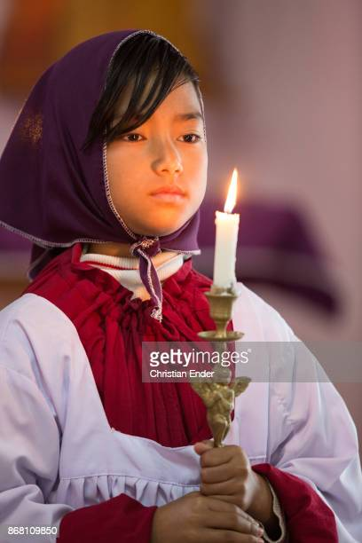 A young girl as a altar server with a tunicle is holding a candle while a ceremony inside a church in Kalimpong