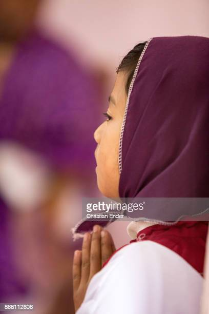 A young girl as a altar server with a tunicle is praying inside a church in Kalimpong
