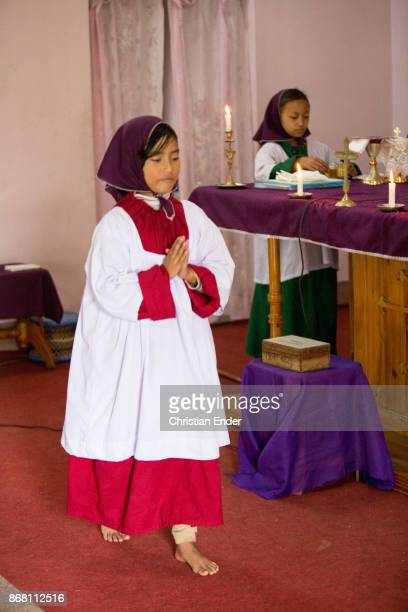 A young girl as a altar server with a tunicle is walking barefoot with folded hands beside a altar inside a church in Kalimpong and is praying