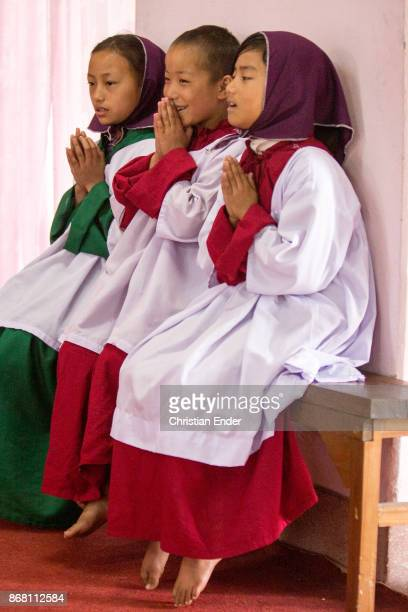 A young girl as a altar server with a tunicle singing barefoot inside a church in Kalimpong