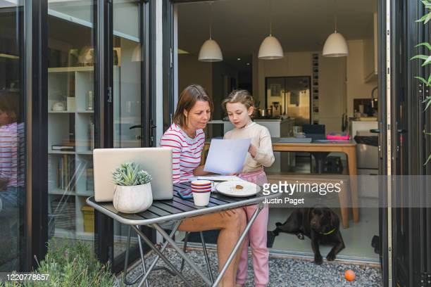 young girl asking her mum for help whilst she works from home - working stock pictures, royalty-free photos & images