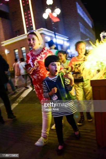 young girl at a night market in urumqi - sergio amiti stock pictures, royalty-free photos & images