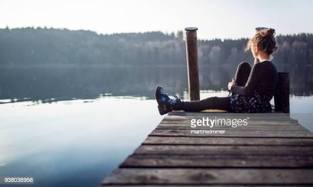 junges Mädchen auf einem Holzsteg am See in Österreich