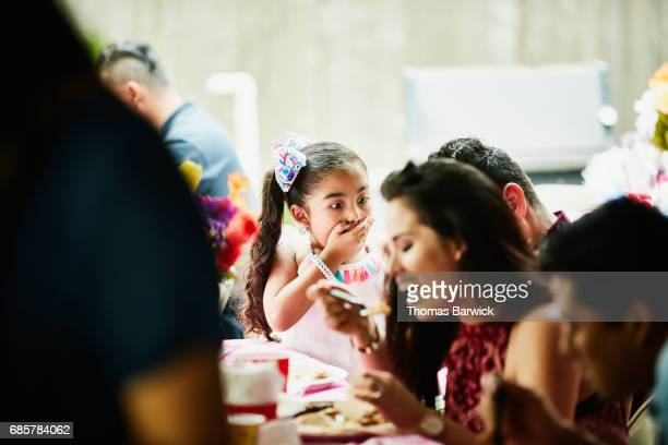 Young girl at family birthday with hand over mouth and surprised expression