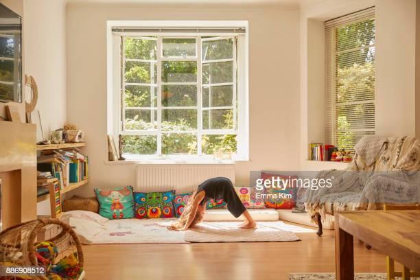 young girl at home, bent over in yoga position - little girls bent over fotografías e imágenes de stock