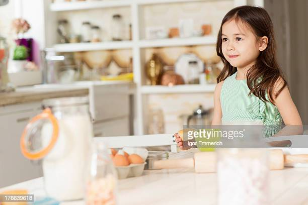 Young girl at kitchen counter measuring ingredients